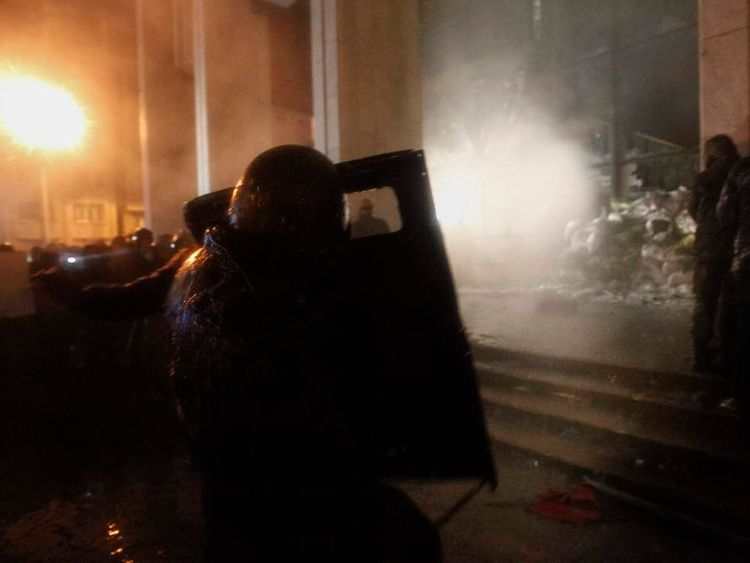 "Anti-government protesters try to enter the ""Ukrainian house"" where riot police were located during a rally in Kiev"