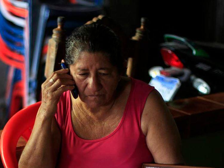 Maria Julia Alvarenga, mother of castaway Jose Salvador Alvarenga, shows a photo of his son, in their fishing hometown of Ahuchapan