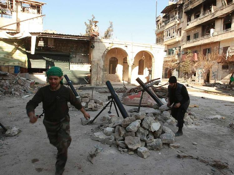 Free Syrian Army fighters react as they launch mortar shells towards forces loyal to Syria's President Bashar al Assad in Aleppo