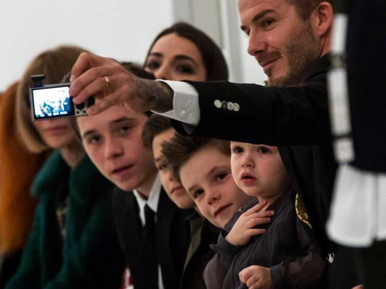 David Beckham takes a 'selfie' of himself and his children before the Victoria Beckham Fall 2014 collection during New York Fashion Week
