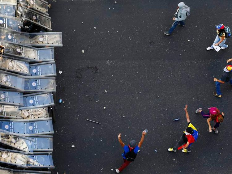 Demonstrators throw stones at riot police taking cover behind their shields, during an anti-government protest in Caracas