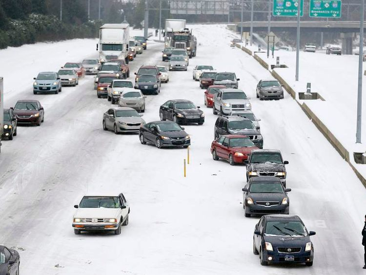 Motorists come to a standstill on a freeway as it snows in Charlotte