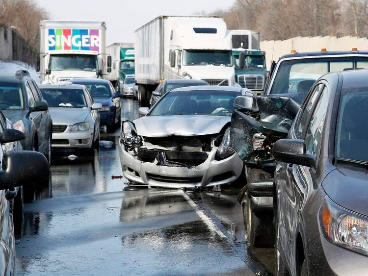 Smashed vehicles await assistance as dozens of flipped-over cars, jack-knifed tractor-trailers and vehicles skidded off the Pennsylvania Turnpike during the morning commute, shutting down the major thoroughfare near the Bensalem interchange in Pennsylvania