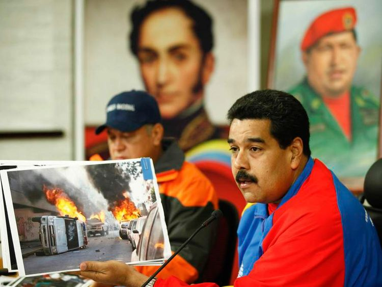 Venezuela's President Maduro shows pictures of violent incidents during the recent protest during a national broadcast at Miraflores Palace in Caracas