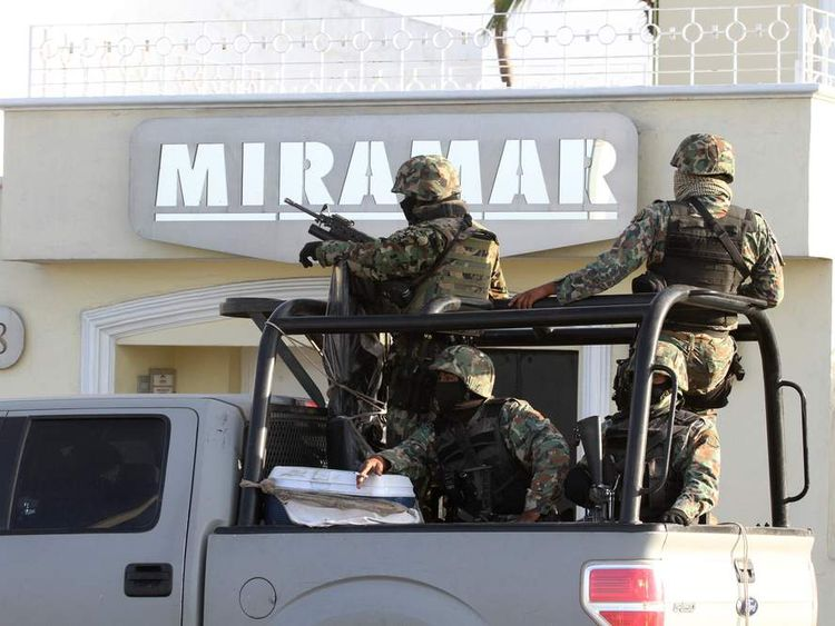 Military personnel stand atop a truck outside the Miramar building during a raid in Mazatlan