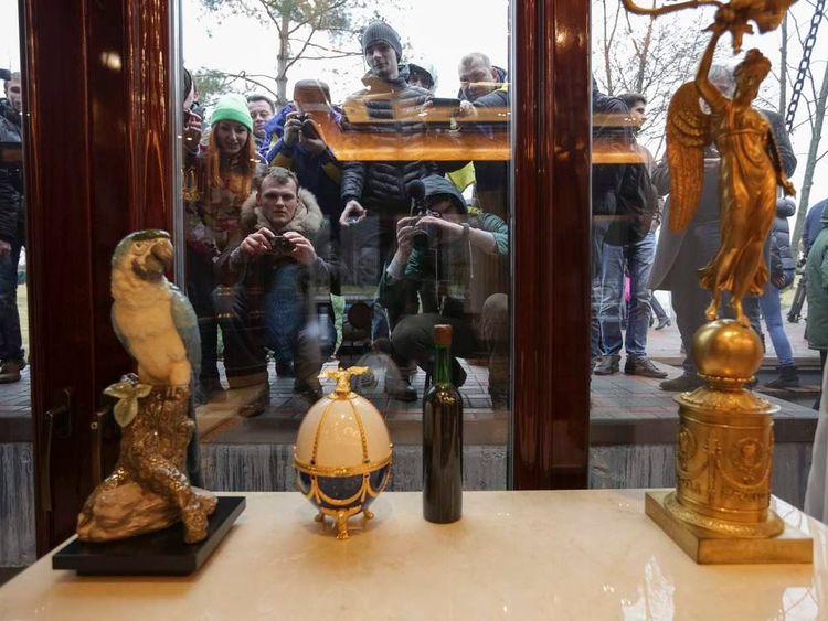People look through windows of the Mezhyhirya residence of Ukraine's President Yanukovych.