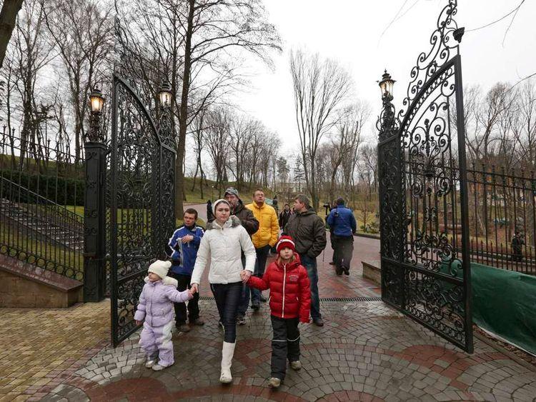 People walk on the grounds of the Mezhyhirya residence of Ukraine's President Viktor Yanukovych in the village of Novi Petrivtsi outside Kiev