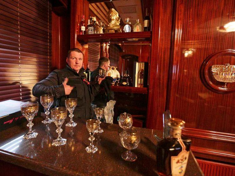 A man gestures behind the interior bar inside the residence of Ukraine's President Viktor Yanukovych in the village of Novi Petrivtsi outside Kiev.