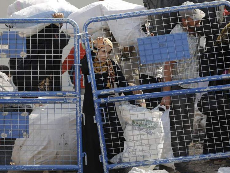 Syrian refugees carry their belongings as they cross into Turkey at Akcakale border gate in Sanliurfa province, Turkey