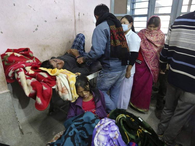 Medics tend to people who were injured after an earthquake in Imphal.