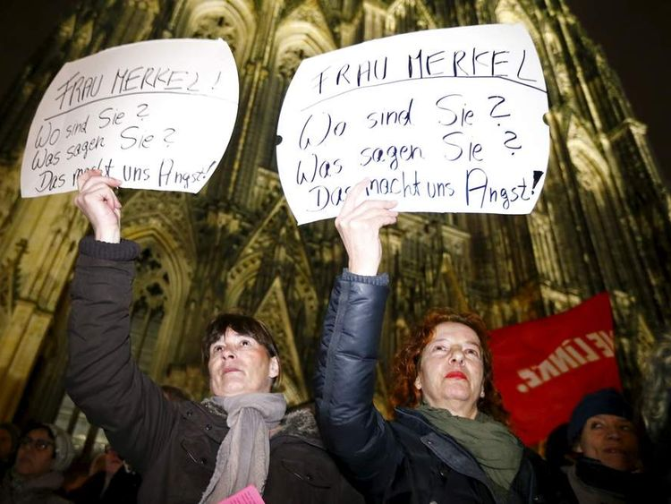Women hold up placards during a protest in front of the Cologne Cathedral