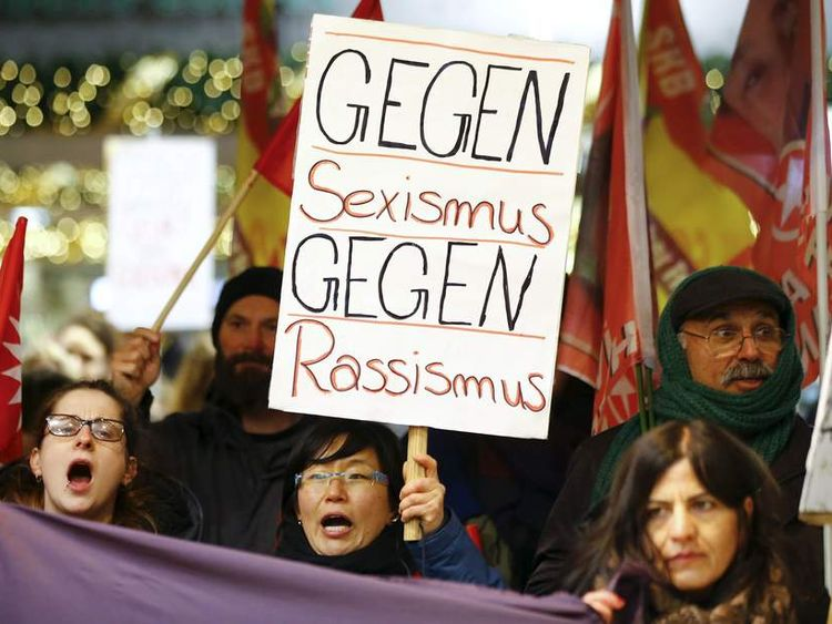"Women shout slogans and hold up a placard that reads ""Against Sexism - Against Racism"" as they march through the main railway station of Cologne"
