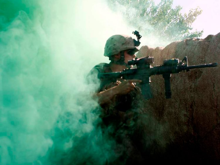 A U.S. Marine, from the 24th Marine Expeditionary Unit, holds his position as Taliban fighters open fire near Garmser in Helmand Province of Afghanistan
