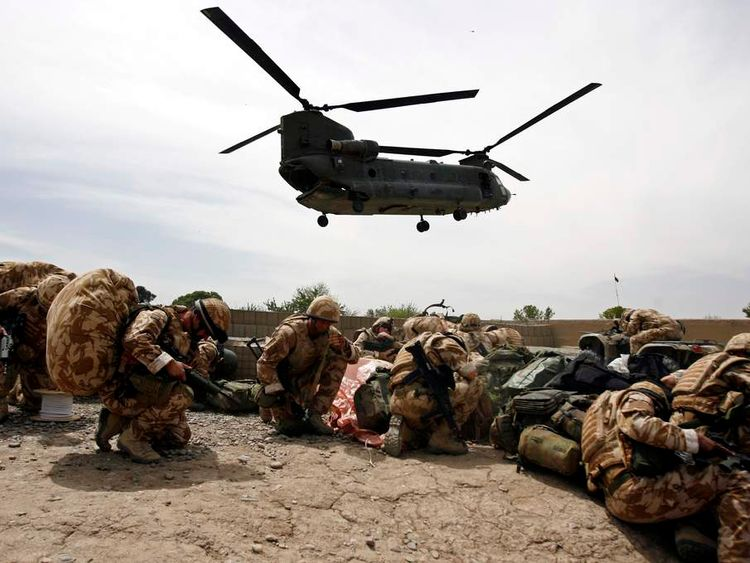 British soldiers take cover as a helicopter lands at Musa Qala in Helmand province