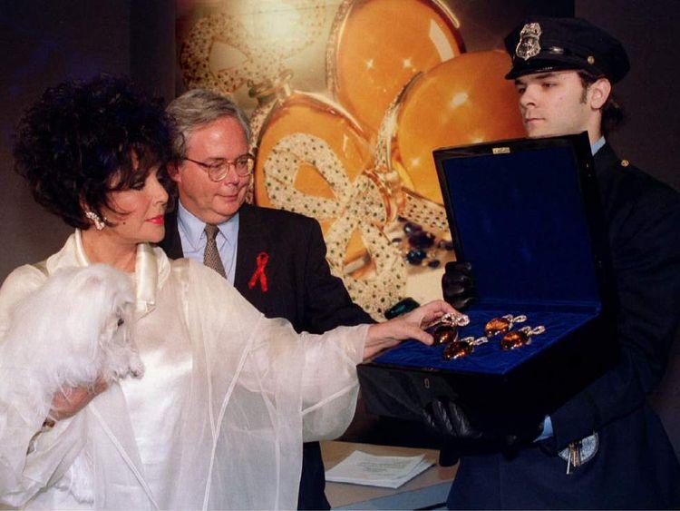 Actress Elizabeth Taylor poses with Elizabeth Arden executive Joseph X. Spellman (C) and a set of he..