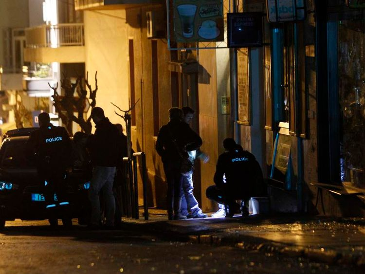 Police officers search for evidence near the home of a prominent Greek ship owner following a bomb explosion in central Athens