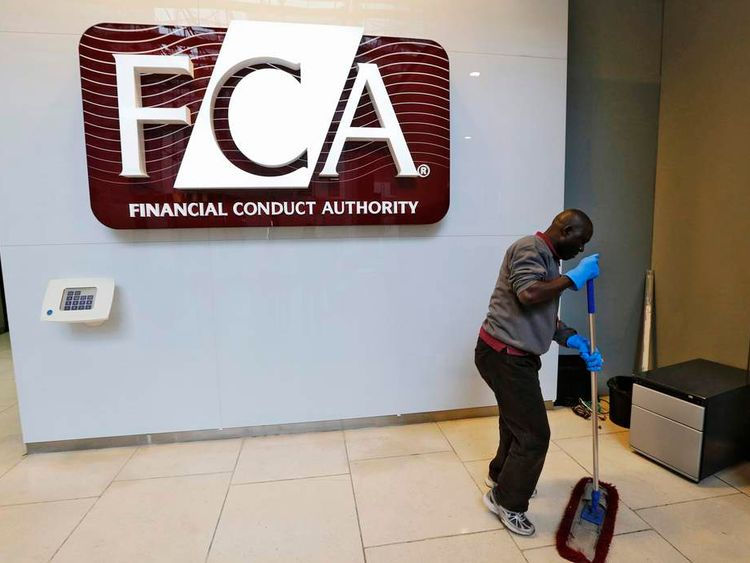 A maintenance worker cleans the entrance area of the headquarters of the new Financial Conduct Authority in the Canary Wharf business district of London