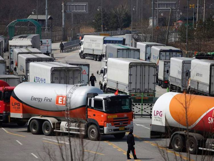 South Korean security guards keep watch as South Korean trucks return to South Korea's CIQ (Customs, Immigration and Quarantine) after they were banned from entering the Kaesong industrial complex in North Korea, in Paju