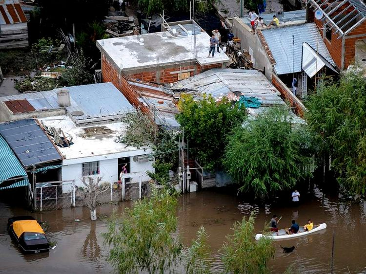 Residents stand on the roofs of their homes after heavy rains in La Plata