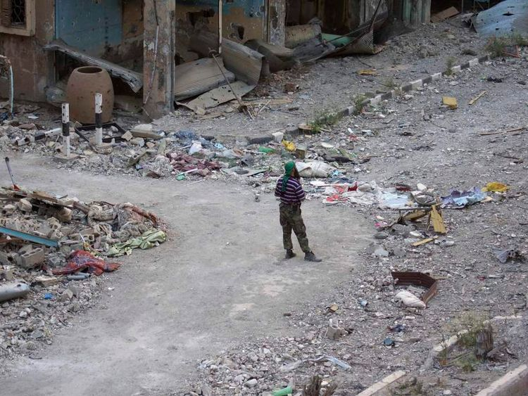 A member of the Free Syrian army stands on a street filled with debris in Deir al-Zor
