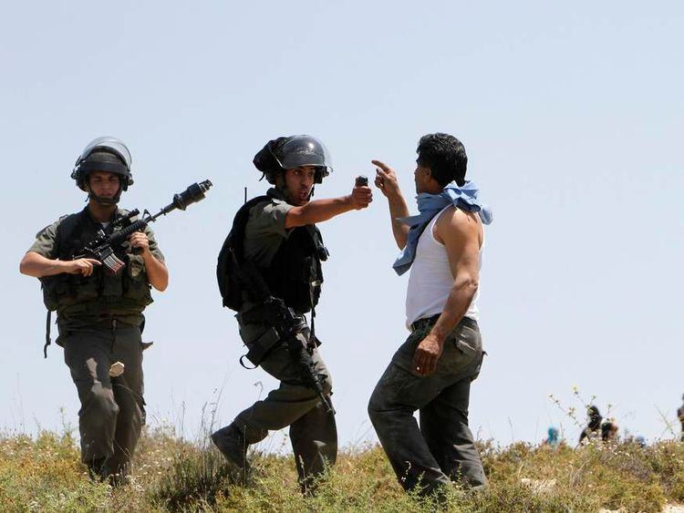 An Israeli border police officer aims pepper spray towards a Palestinian during clashes near Nablus