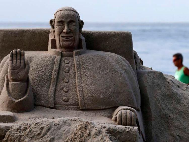 A man runs behind a Pope Francis sand sculpture in Rio de Janeiro