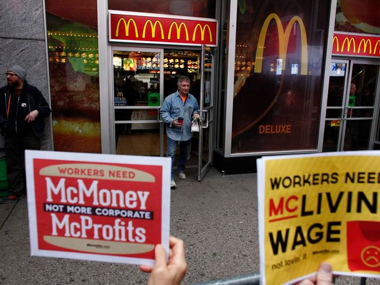 A customers exits a McDonald's restaurant as members of 'MoveOn' shout slogans against McDonald's in front of the restaurant in Times Square, New York