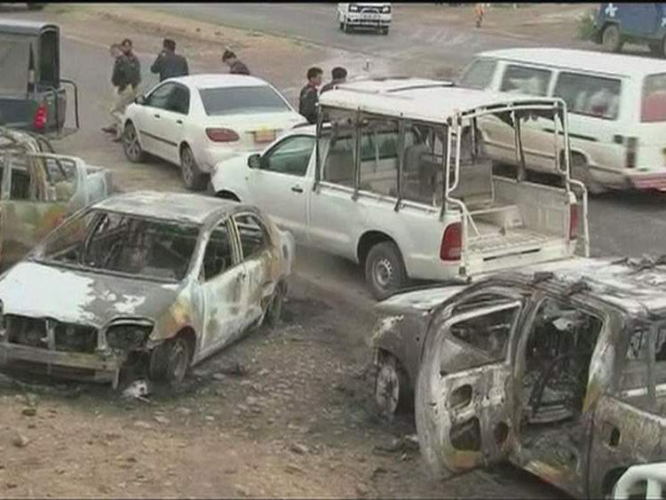 Smoldering vehicles at the scene of a militant attack on a police station in Peshawar, Pakistan.