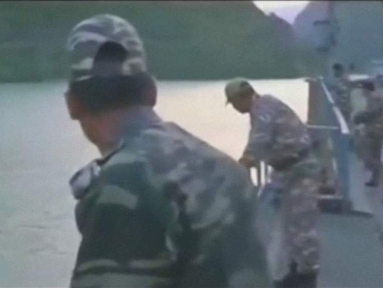 Indian soldiers search for missing students swept away in a river in northern India after a nearby dam releases water