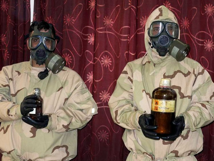 Soldiers wearing gas masks hold bottles containing chemical materials during a news conference at the Defence Ministry in Baghdad