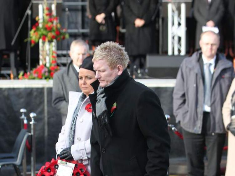 Survivor Stephen Gault, who lost his father Sammy, lays a wreath the town's war memorial