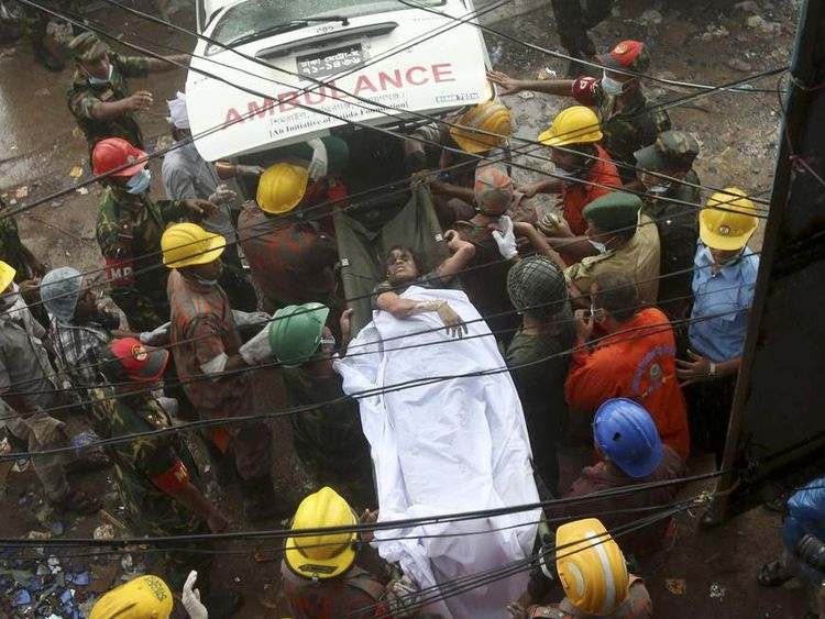 A survivor is carried on a stretcher into a waiting ambulance in Dhaka