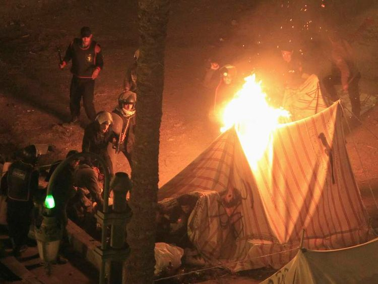 An anti-Mursi demonstrator tries to escape from a tent set on fire by riot police at Tahrir Square in Cairo