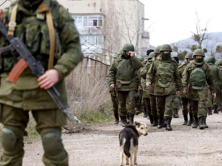 Armed men, believed to be Russian servicemen, walk outside a Ukrainian military base