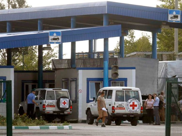 """Cars of the Red Cross and trucks of a Russian convoy carrying humanitarian aid for Ukraine are seen at a Russia-Ukraine border crossing point """"Donetsk"""" during a control check in Rostov Region"""