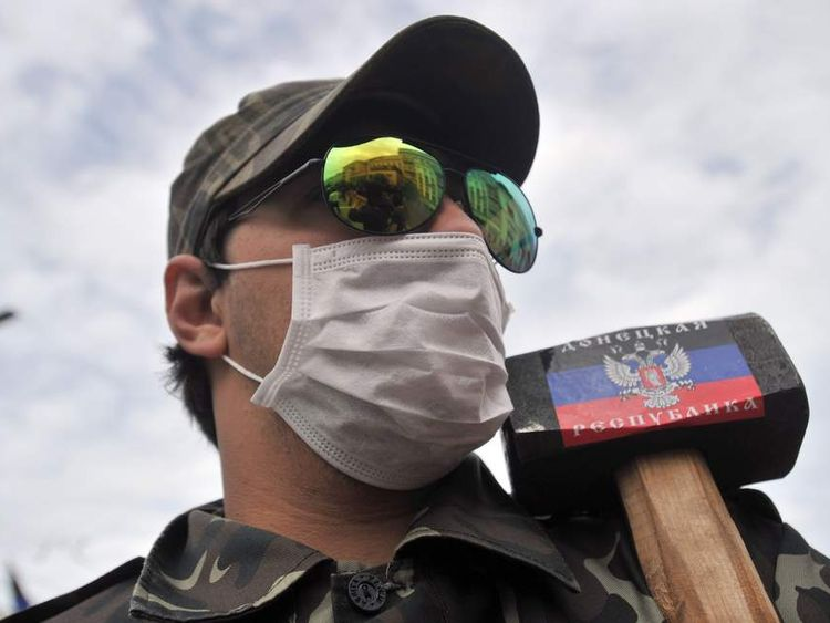 A pro-Russia activist in eastern Ukraine holds a hammer with the flag of the so-called Donetsk People's Republic