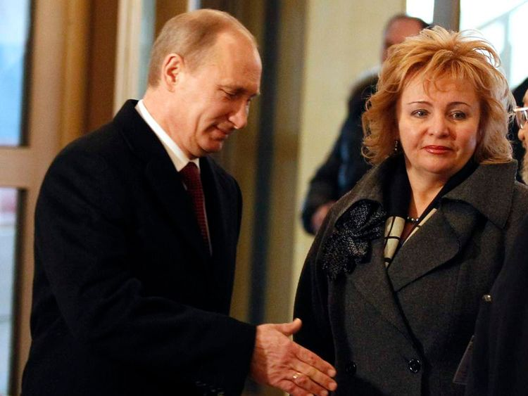 Russian PM Putin stands with his wife Lyudmila after arriving to vote in a polling station in Moscow