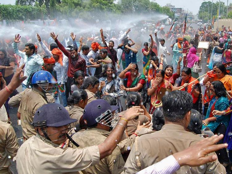 Members of the BJP are hit by water cannon during a protest against rape