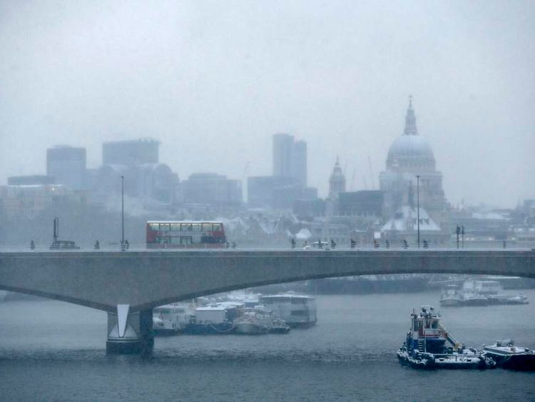 Commuters walk over Waterloo Bridge in the snow in central London