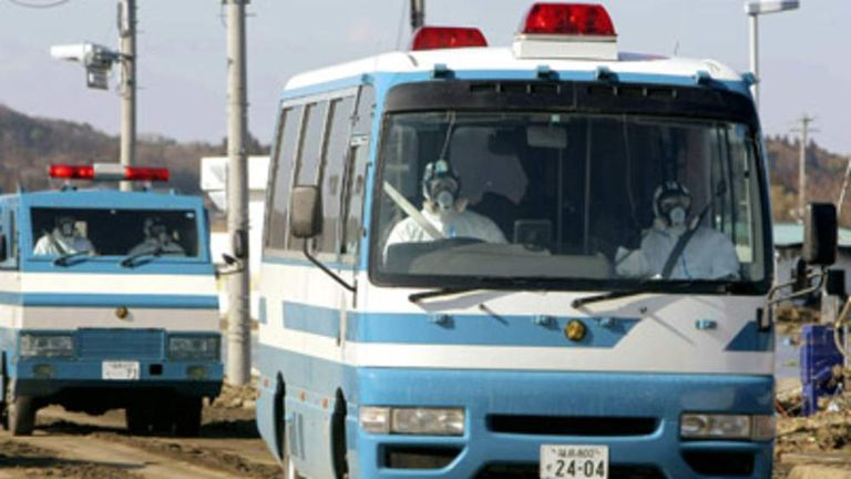 Police officers in protective suits drive vehicles at Minamisoma city in Fukushima prefecture near the nuclear plant on March 12, 2011.