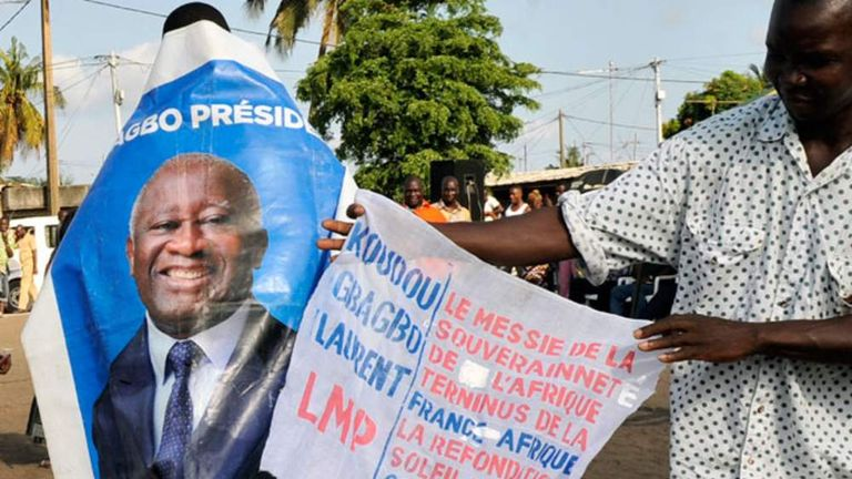 "A supporter of the former president wears a banner reading ""Ghagbo for President"""