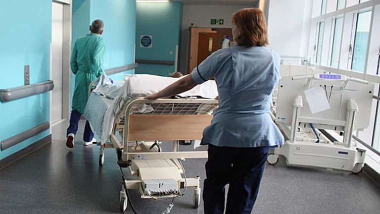 Staff at an NHS hospital take a patient to an operating theatre