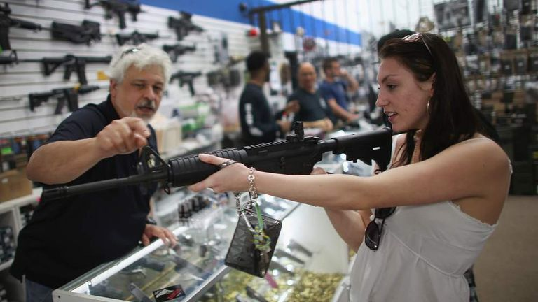 A customer tries an AR-15 for size at the National Armory gun store in Florida