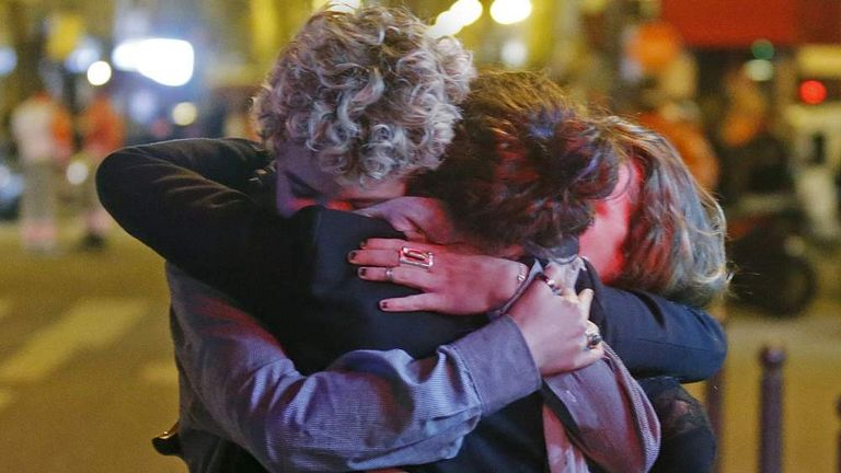 People hug on the street near the Bataclan concert hall following fatal attacks in Paris, France,