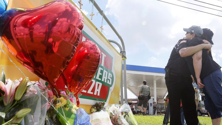 Mourners gather at a makeshift memorial for three police officers who were shot and killed in Baton Rouge, Louisiana