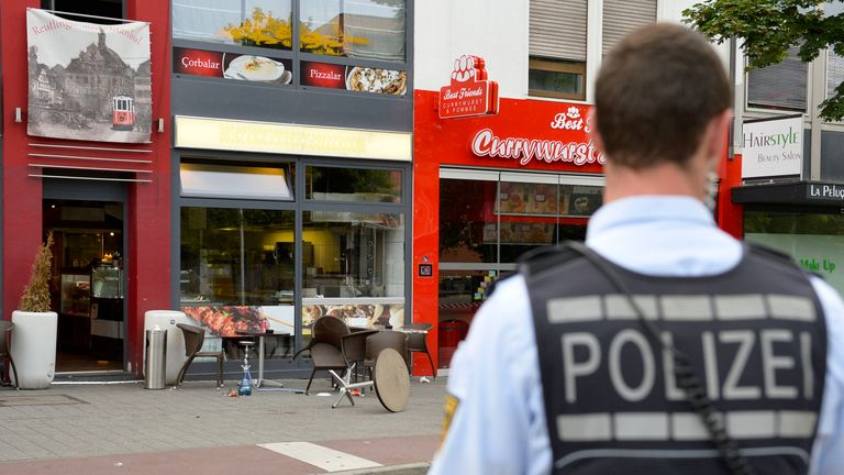 A police officer stands in front of a fastfood restaurant in Reutlingen, Germany, where a Syrian asylum-seeker killed a woman and injured two people with a machete