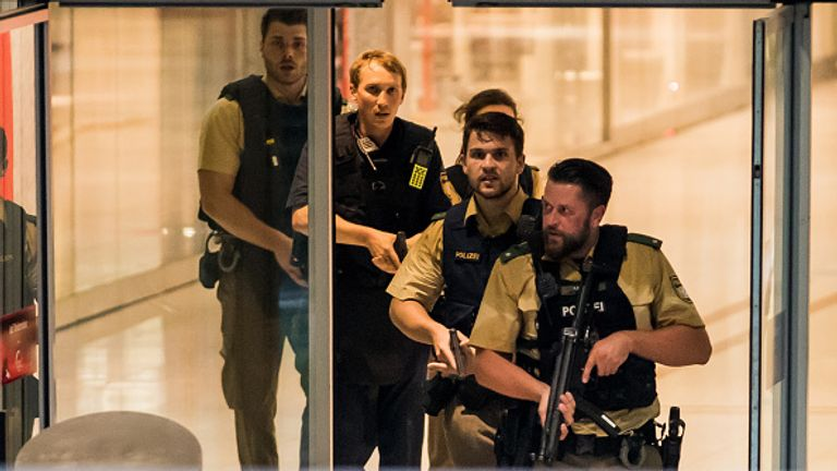 Police walk into the shopping centre in Munich