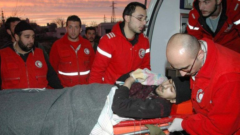 Syrian Red Crescent staff help a wounded man after civilians were evacuated from rebel-controlled districts that were besieged by the army, into a government-ruled area, in the central Syrian city of Homs