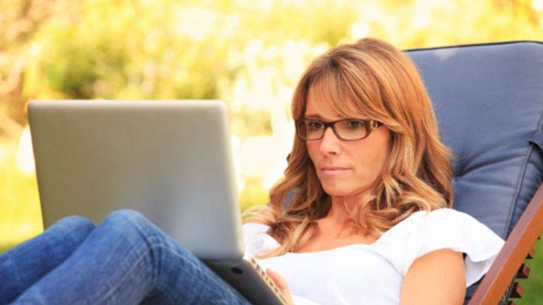 Mature woman working in the garden on her laptop.