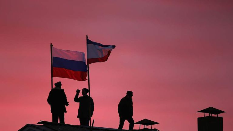 Cossack men install a Russian flag and a Crimean flag on the roof of the City Hall building in Bakhchysarai